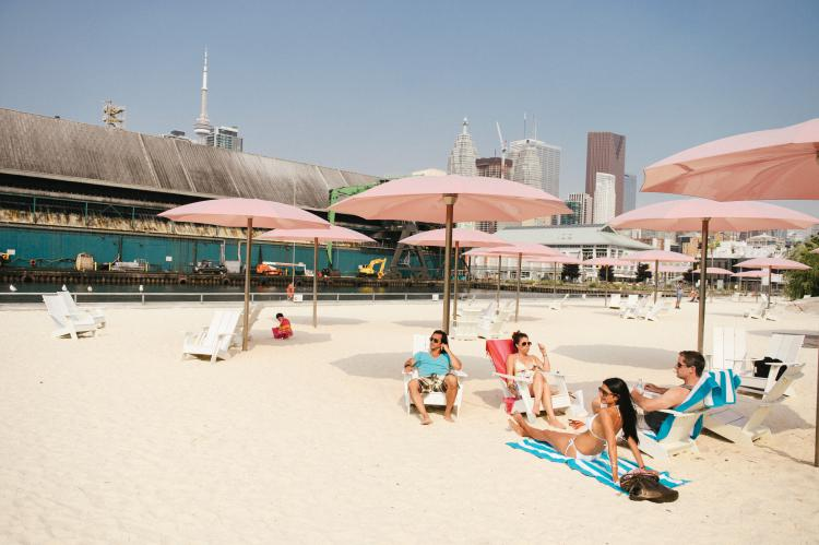 Beachgoers soak up the sun while the skyscrapers glisten in the background Image C/O Canadian Tourism Commission